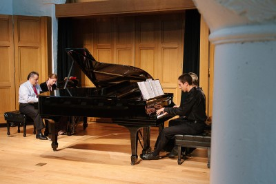 Two students and one teacher in a piano class