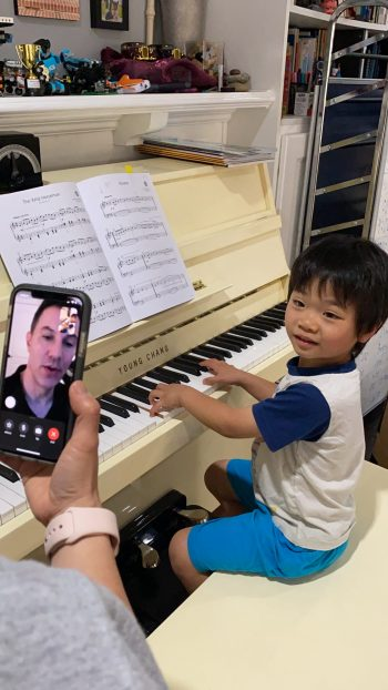 Young boy at piano facetiming with teacher