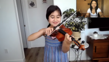 Young violin student taking a virtual lesson